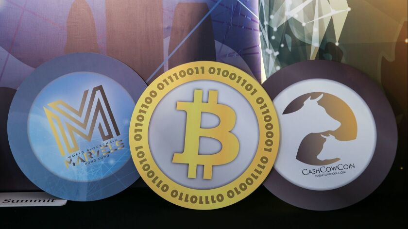 Logos of cryptocurrencies are displayed during the World Blockchain Marvels summit in Hong Kong last month.