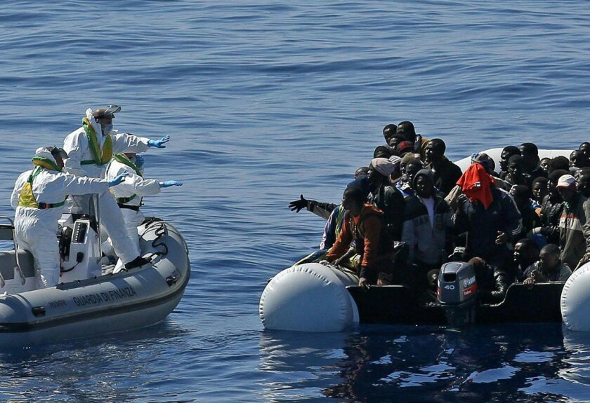 In this photo made available Thursday, April 23, 2015, an Italian Financial Police rescue unit approaches an inflatable dinghy crowded with migrants off the Libyan coast, in the Mediterranean Sea, Wednesday, April 22, 2015.  European Union leaders gathering for an extraordinary summit are facing ca
