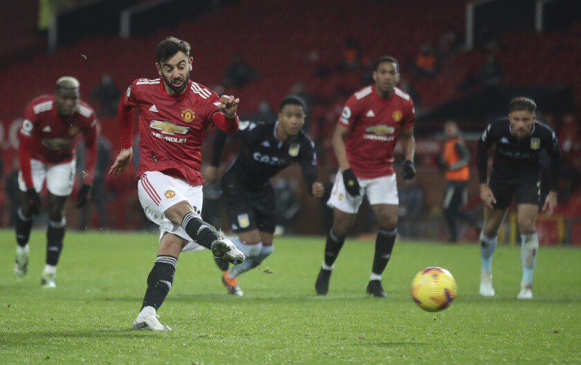 Manchester United's Bruno Fernandes shoots and scores his sides 2nd goal from the penalty spot during the English Premier League soccer match between Manchester United and Aston Villa at Old Trafford in Manchester, England, Friday, Jan. 1, 2021. (Carl Recine/ Pool via AP)
