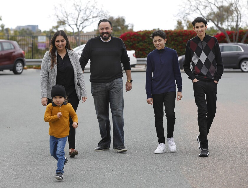 Erik Hoyo, his wife, Laura and their sons Ezekiel, 15, and Adrian, 17, right, were all sickened with Covid-19. Their son Mateo, 3, left, was not infected.