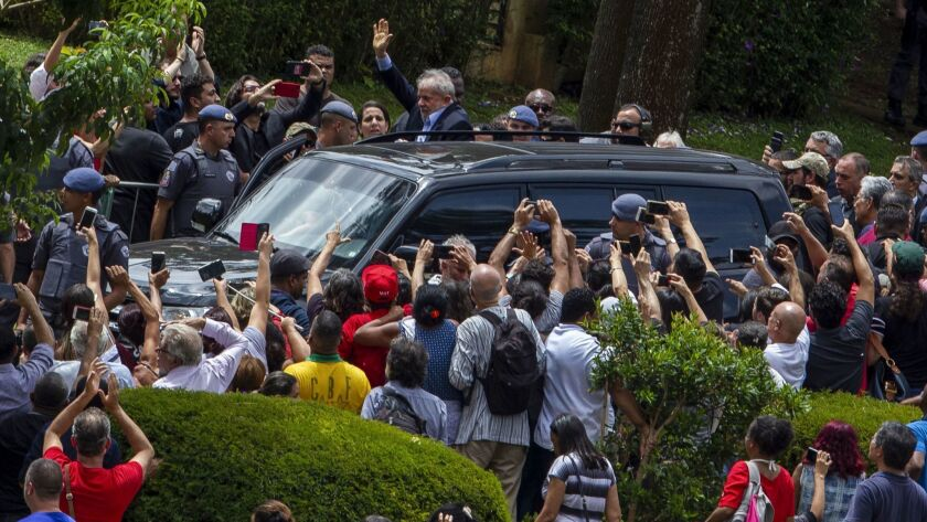 Brazilian former president Luiz Inacio Lula da Silva waves to supporters as he leaves the cemetery in Sao Paulo, Brazil, where he attended his grandson's funeral Saturday.