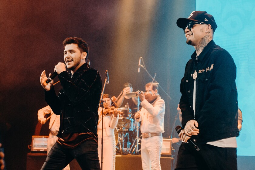 On stage, with violin players in the background, Christian Nodal and Gera MX hold microphones.