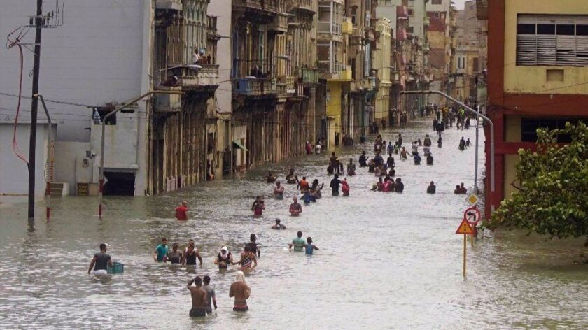 People move through flooded streets in Havana after the passage of Hurricane Irma, in Cuba, Sunday,