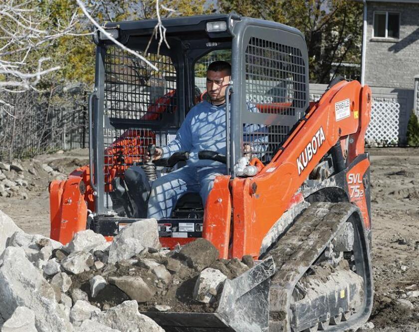 Un trabajador de construcción retira las rocas del terreno de una nueva casa. EFE/Archivo
