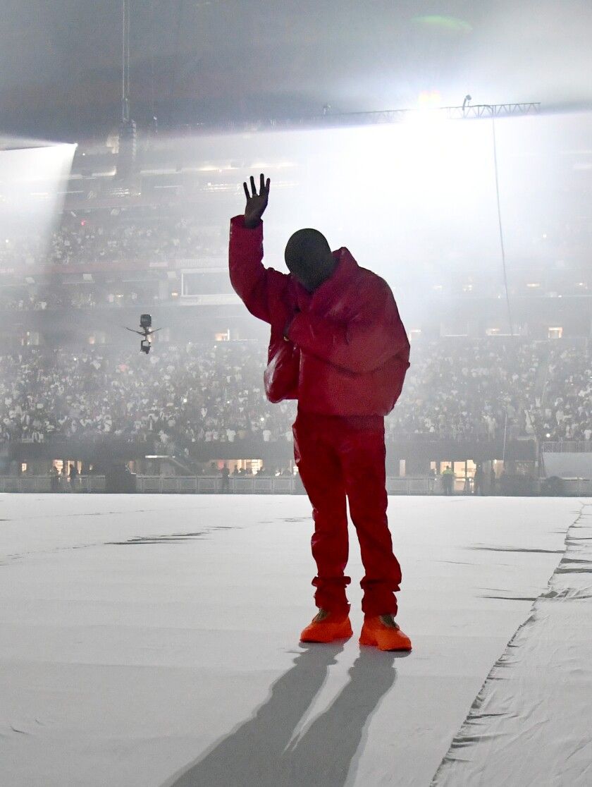 Kanye West in red jacket and pants