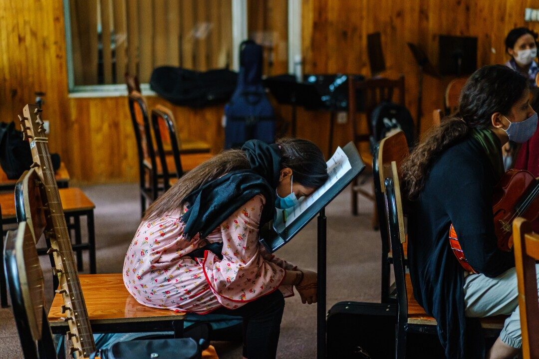 A girl rests her head on a music stand.