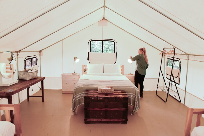 A woman standing in a large family tent at Mendocino Grove campground.