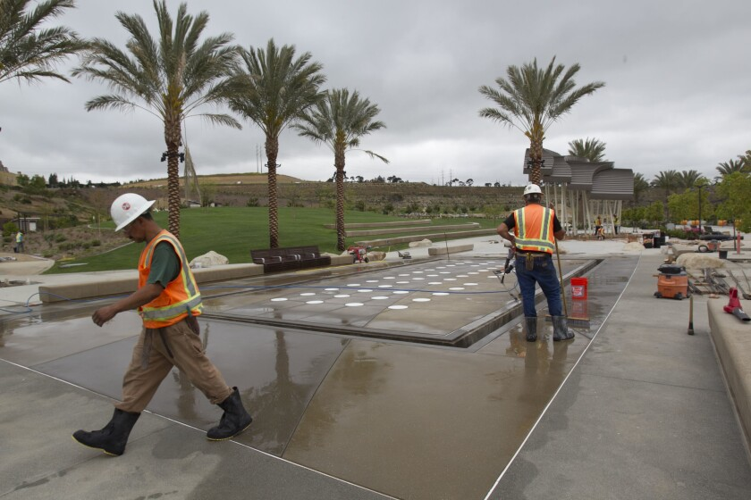 Workers clean the cement around the interactive water feature at the interactive fountain.