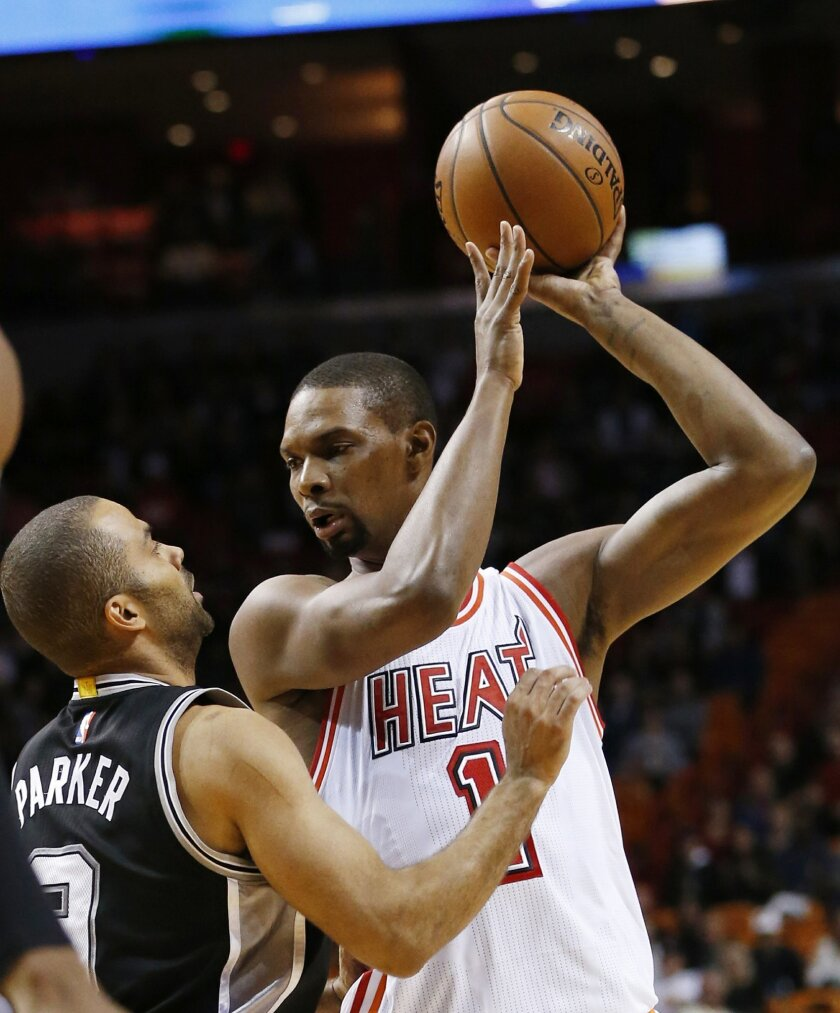 In this Tuesday, Feb. 9, 2016, photo, Miami Heat forward Chris Bosh (1) looks for an opening past San Antonio Spurs guard Tony Parker (9) during the first half of an NBA basketball game in Miami. Bosh released a video Monday, Aug. 29, on Snapchat of him going through a non-contact workout, includin