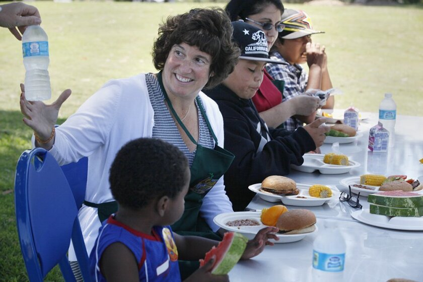 SDUSD superintendent Cindy Marten accepts a bottle of water as she sits down to have lunch with some of the children participating in the summer lunch program on Wednesday.