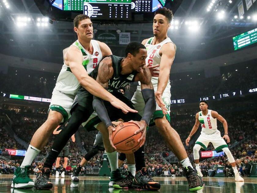 Rondae Hollis-Jefferson (c) de los Nets de Brooklyn rodeado por Brook Lopez (i) y Malcolm Brogdon (d) de los Bucks de Milwaukee durante el partido de la NBA entre los Nets de Brooklyn y los Bucks de Milwaukee en el Fiserv Forum en Milwaukee, Wisconsin (EE.UU.), hoy, 29 de diciembre de 2018. EFE