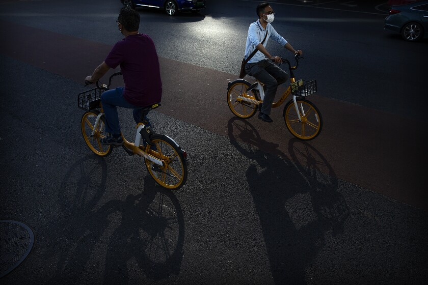 People wear face masks to protect against the coronavirus as they ride bicycles on a street in the central business district in Beijing, Wednesday, July 15, 2020. China is further easing restrictions on domestic tourism after reporting no new local cases of COVID-19 in nine days. (AP Photo/Mark Schiefelbein)