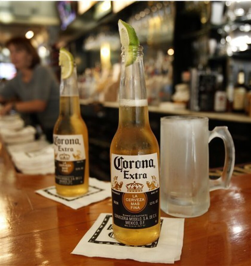 This Oct. 5, 2011 photo, shows Corona Extra beers, sporting lime wedges, on the bar at Rick's Cafe in Chagrin Falls, Ohio. The maker of Robert Mondavi wine and Svedka vodka said Thursday, Oct. 6, 2011, its second-quarter profit jumped 78 percent to $162.7 million on lower costs and improved wine and spirits sales in North America. (AP Photo/Amy Sancetta)