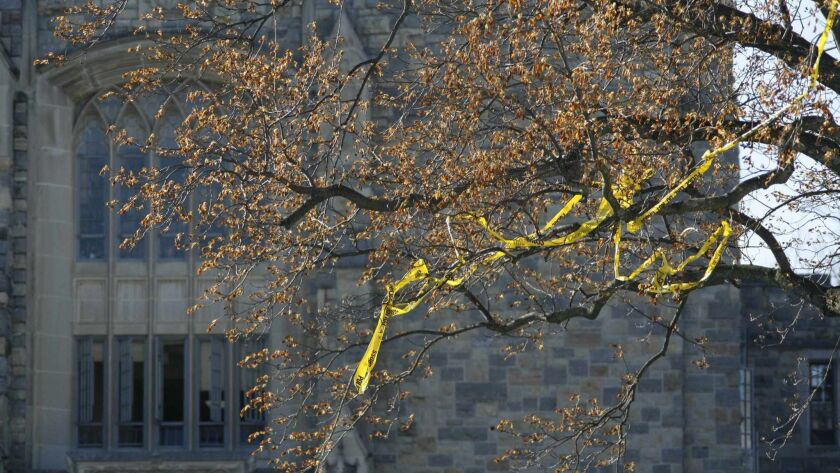 Police tape hangs in the trees in front of Norris Hall on the campus of Virginia Tech Monday, April