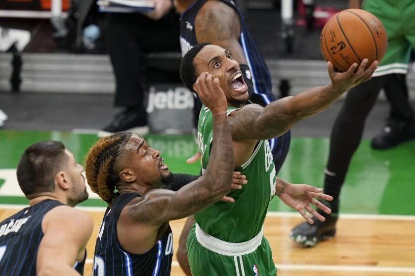Boston Celtics guard Jeff Teague goes to the basket against the defense of Orlando Magic center Nikola Vucevic, left, and guard Jordan Bone during the first half of an NBA basketball game Friday, Jan. 15, 2021, in Boston. (AP Photo/Elise Amendola)