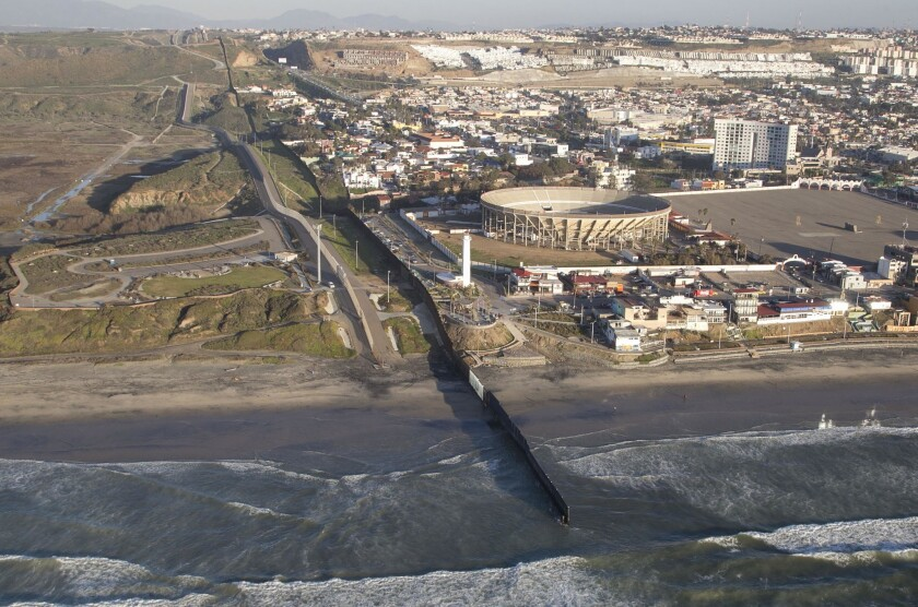 An aerial photo flight of the U.S. Mexico border in California at the Pacific Ocean where the border fence ends in the water.