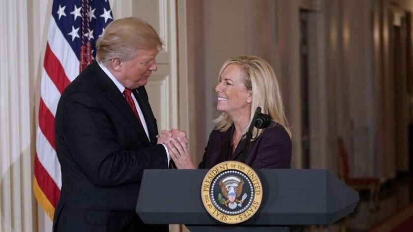 Kirstjen Nielsen shakes hands with President Trump in front of a lectern during her nomination announcement