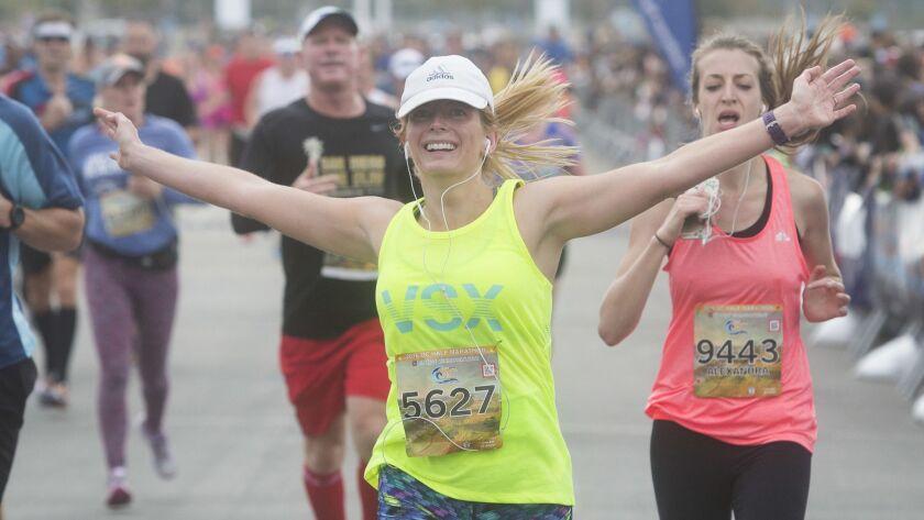Kelly White of Rancho Santa Margarita celebrates as she finishes the12th annual U.S. Bank OC Half Ma
