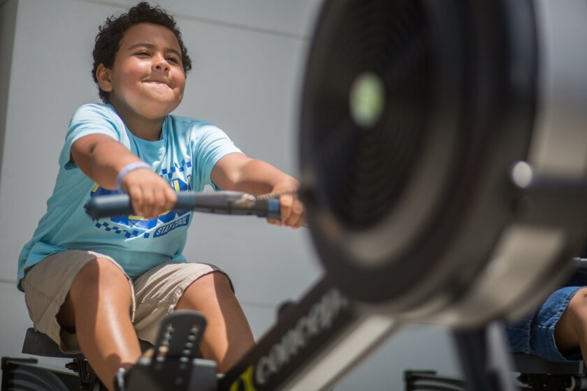 Maxx Lemons, 5, tries to top the best time on a rowing machine Saturday at the center.