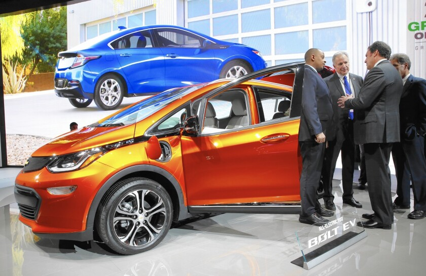 Transportation Secretary Anthony Foxx, left, and NHTSA Administrator Mark Rosekind listen to Mark Reuss of General Motors talk about the 2017 Chevrolet Bolt electric vehicle at the Detroit auto show.