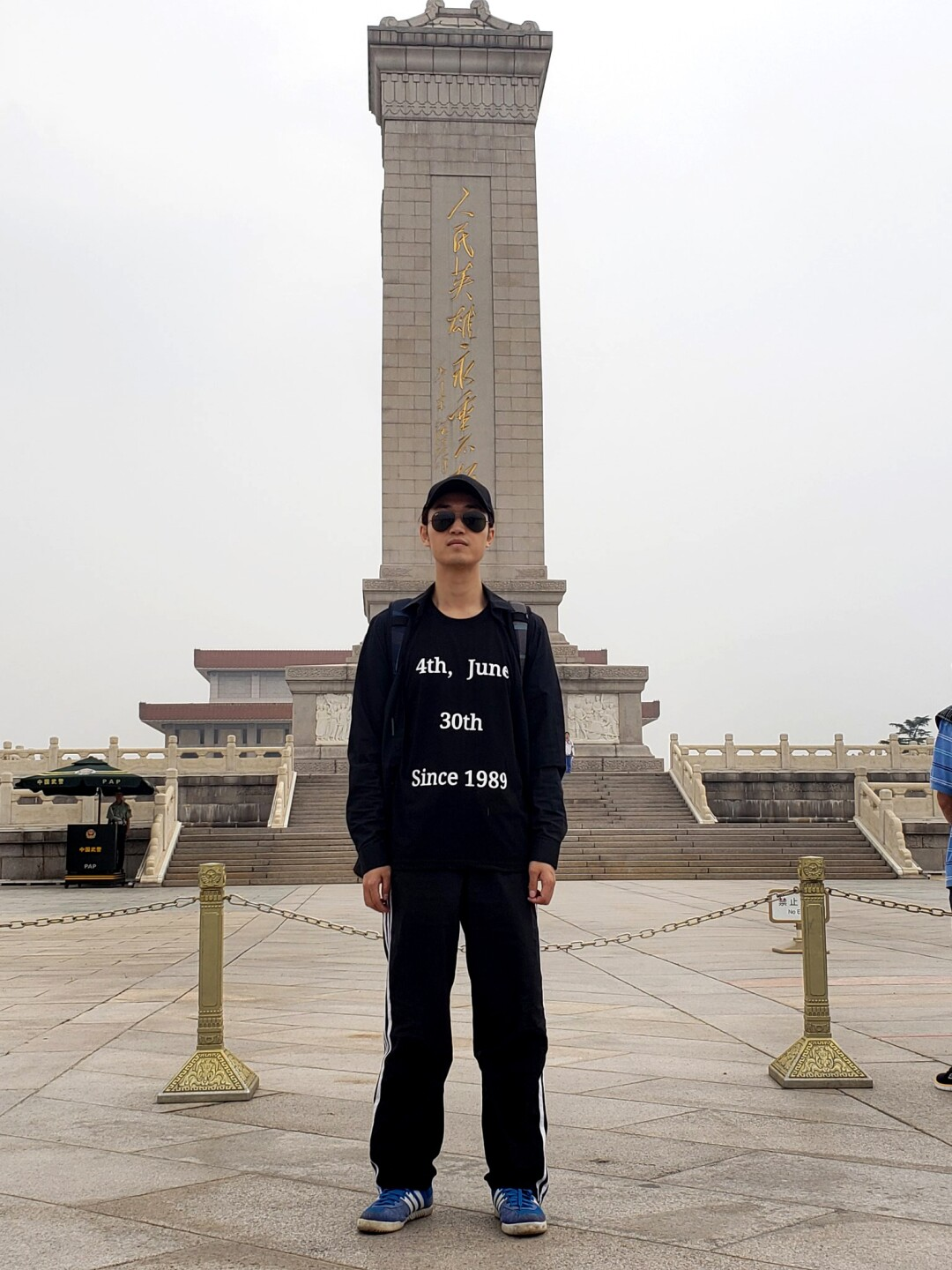 A man dressed all in black stands in front of a beige monument