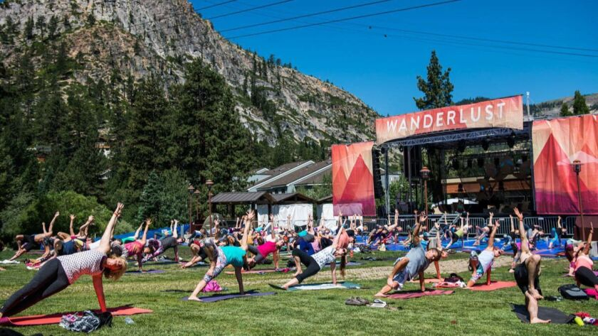 People doing yoga poses on mats on grass next to trees and a mountain at Wanderlust Squaw Valley.