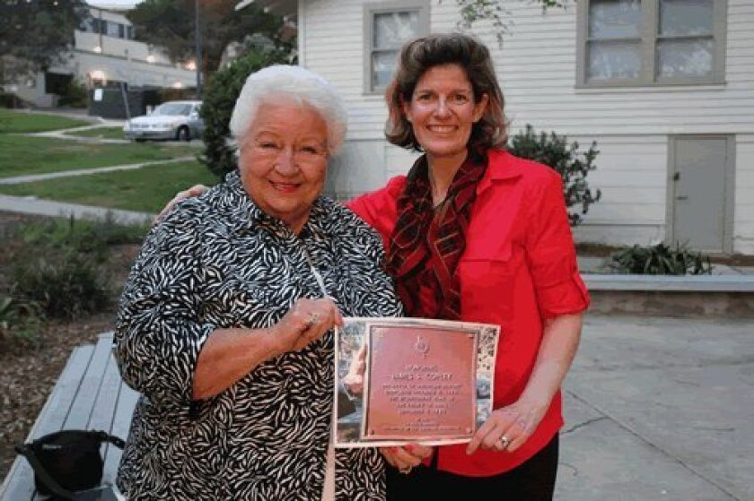 Donna Derrick and Barbara Denny show off a photo of a plaque similar to what they would like placed at The Shores. Ashley Mackin