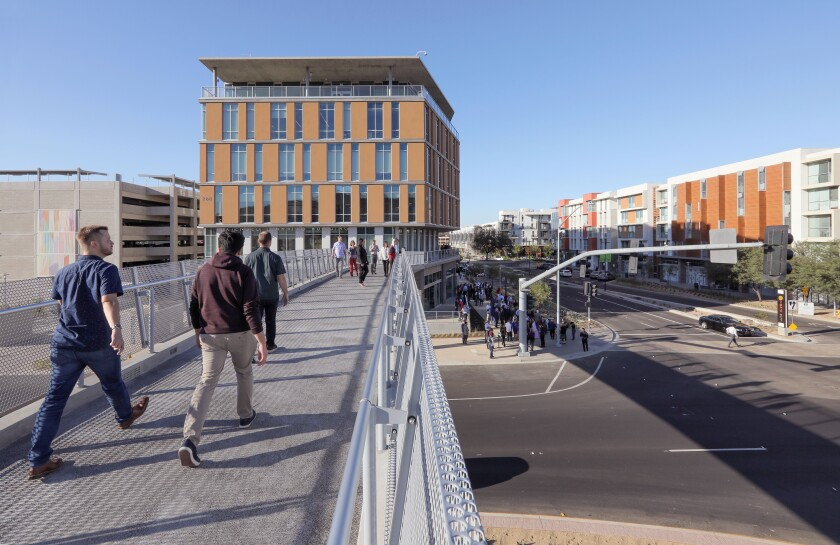People walk on the new pedestrian bridge over Barham Drive linking the school's new Extended Learning Building (above) to the main campus. The Cal State San Marcos Innovation Hub launched at the new Extended Learning building.