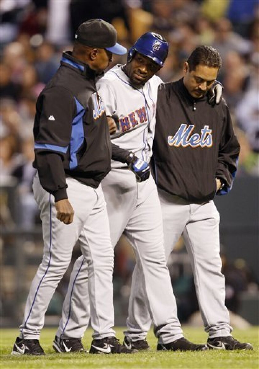 New York Mets manager Willie Randolph, left, helps outfielder Marlon Anderson, center, off the field after Anderson was injured against the Colorado Rockies in the fourth inning of a Major League Baseball game in Denver on Friday, May 23, 2008. (AP Photo/David Zalubowski)