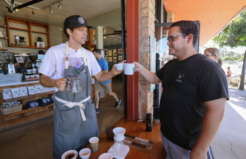 Singer-songwriter Jason Mraz toasts his new locally grown geisha coffee with customer Cory Suarez at Bird Rock Coffee Roasters in La Jolla. Mraz prepared the pour-over for the $35 cup of coffee.