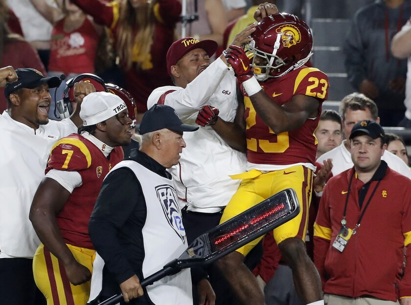 USC running back Kenan Christon (23) celebrates on the sideline after scoring a touchdown against Arizona in the fourth quarter Saturday night at the Coliseum.