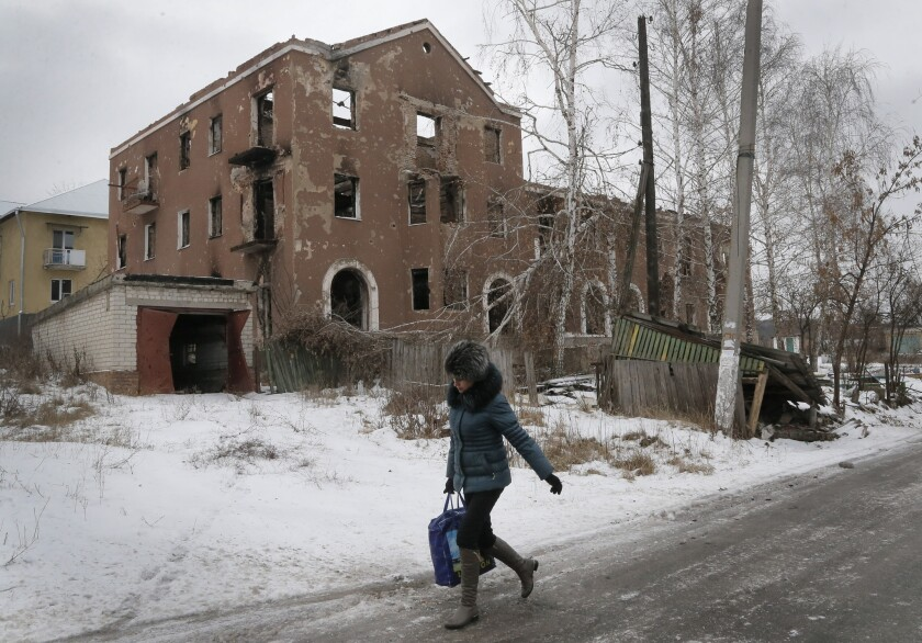 A woman passes by a house destroyed in recent battles between the Ukrainian army and pro-Russian separatists in the Donetsk region of eastern Ukraine.