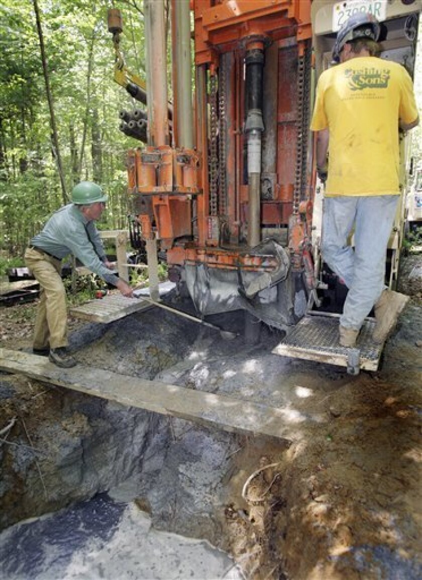 lee Wilder, left, collects bedrock samples as Mo LeClair drills through a deep core of granite in Kingston, N.H., Tuesday, June 2, 2009. New Hampshire is drilling a series of wells to monitor groundwater to allow scientists to check for contamination; learn about how long it takes for rainfall or melting snow to make its way into the supply; and keep tabs on how climate change, population growth and development affect the water. (AP Photo/Jim Cole)
