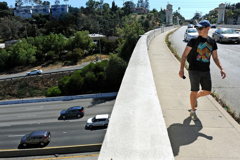 Niall Huffman walks along the Glendale-Hyperion bridge on June 7 while participating in a rally to keep sidewalks on both sides of the bridge as it undergoes retrofitting.