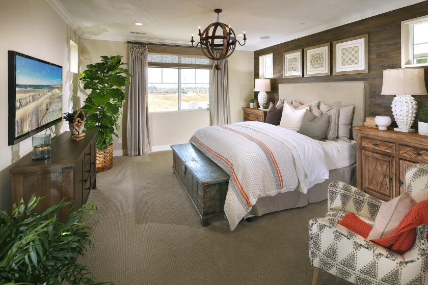 Reclaimed wood walls in a master bedroom capture modern farm style.