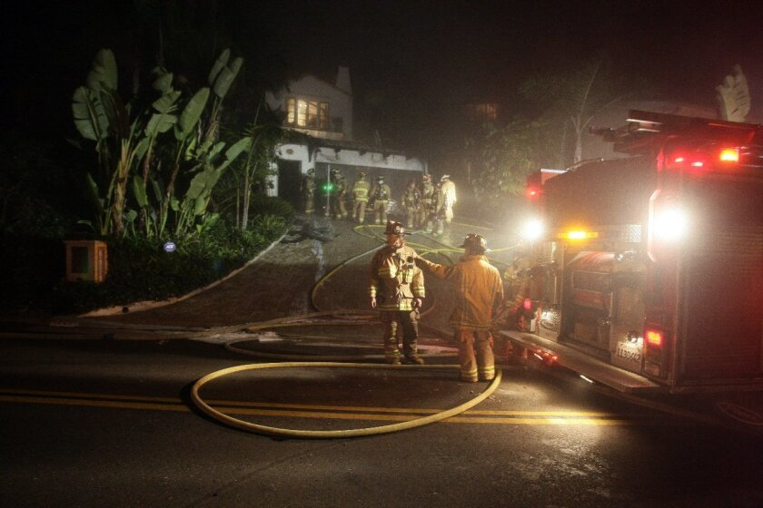 Crews work to extinguish a house fire in the detached garage of a home on Soledad Ave. Photo by Jerod Harris