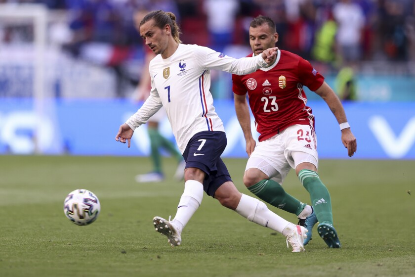 France's Antoine Griezmann gets the ball past Hungary's Nemanja Nikolic during the Euro 2020 soccer championship group F match between Hungary and France, at the Ferenc Puskas stadium, in Budapest, Saturday, June 19, 2021. (Alex Pantling, Pool via AP)