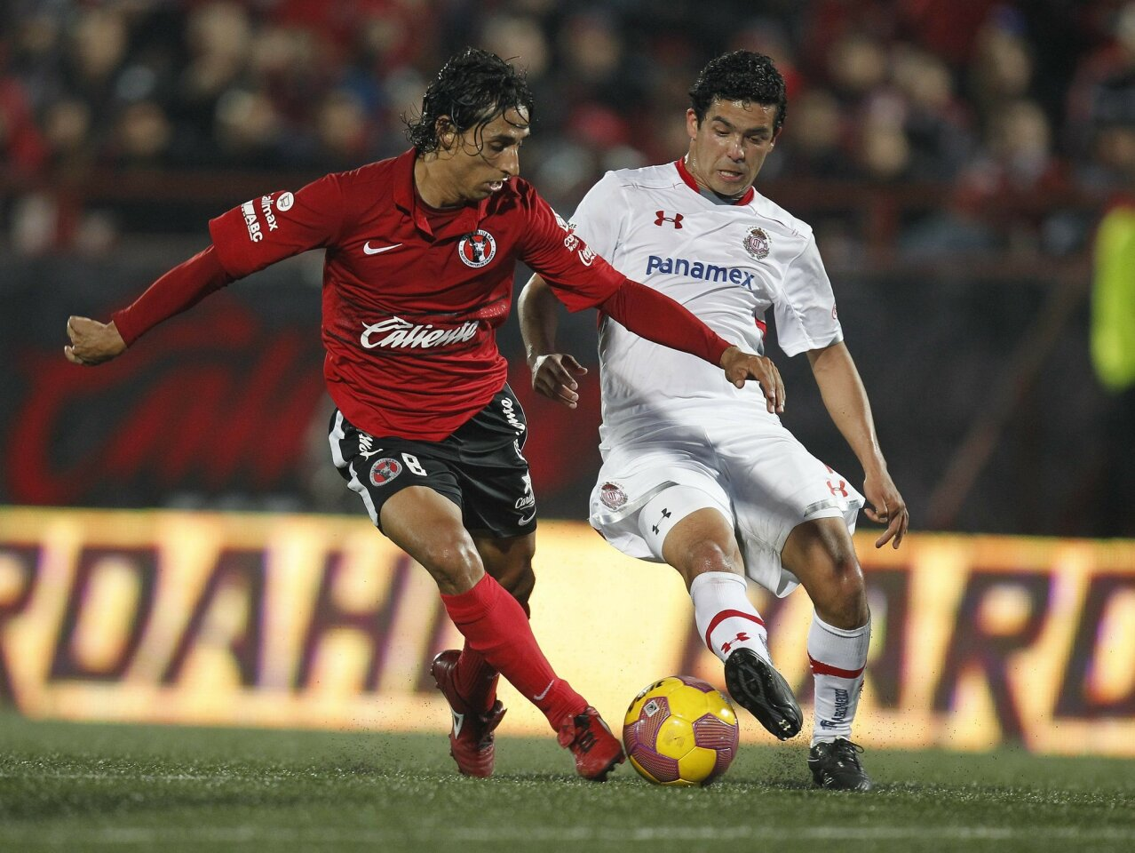 LtoR Club Tijuana #8 Fernando Arce battles for position with #19 of Toluca in the second half.