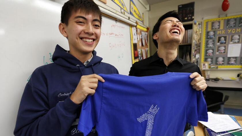 Cedrick Argueta, a la izquierda, estudiante de último año en Lincoln High School en Lincoln Heights, y su maestro de matemáticas, Anthony Yom, muestran una de las camisetas de Cálculo Avanzado que los estudiantes utilizaron en el examen realizado en la pasada primavera. (Al Seib / Los Angeles Times)