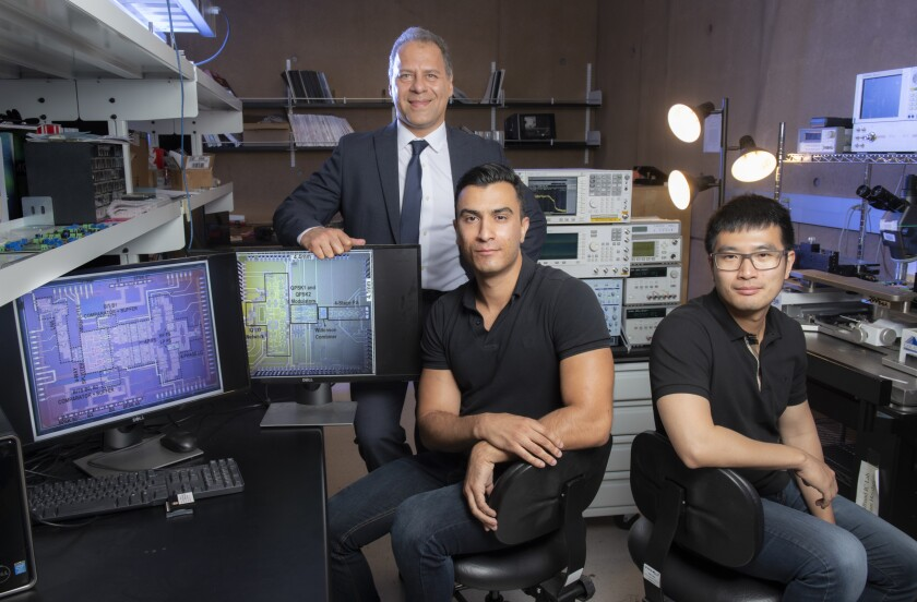 From left, Payam Heydari, professor of electrical engineering & computer science, and lab members Hossein Mohammadnezhad, who earned a doctorate in electrical engineering and computer science this year, and Huan Wang, a doctoral student in the same department stand in their lab.