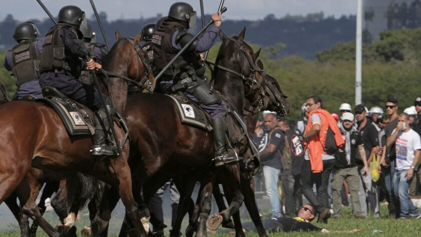 Mounted police charge demonstrators during an antigovernment protest in Brasilia, the Brazilian capi