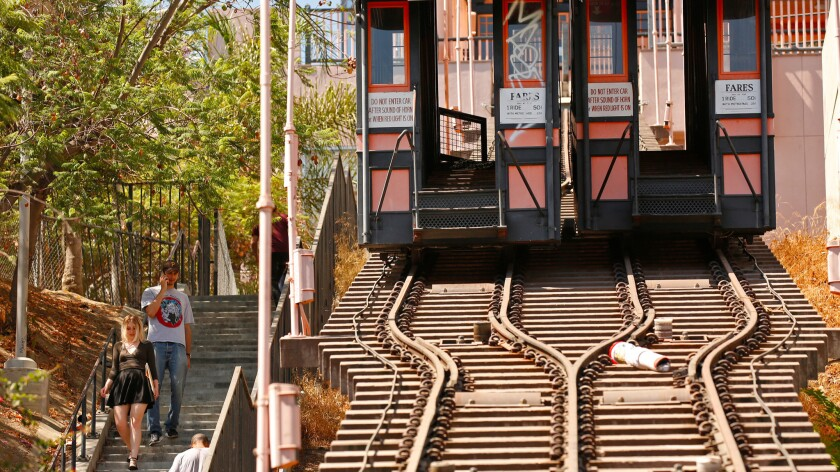 Pedestrians walk down the 153 steps of the stairway parallel to Angels Flight, now covered in graffiti.