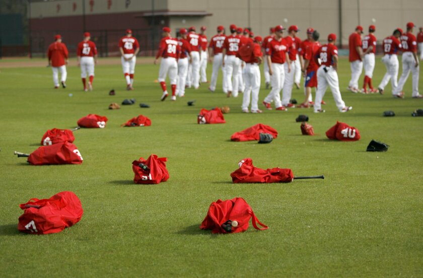 Equipment bags, belonging to Philadelphia Phillies pitchers and catchers, lay on the outfield of Schmidt Field on Monday, Feb. 23, 2015, as the players report to work out during the first day of Spring Training at the Carpenter Complex in Clearwater, Fla.    The first MLB spring training game of th