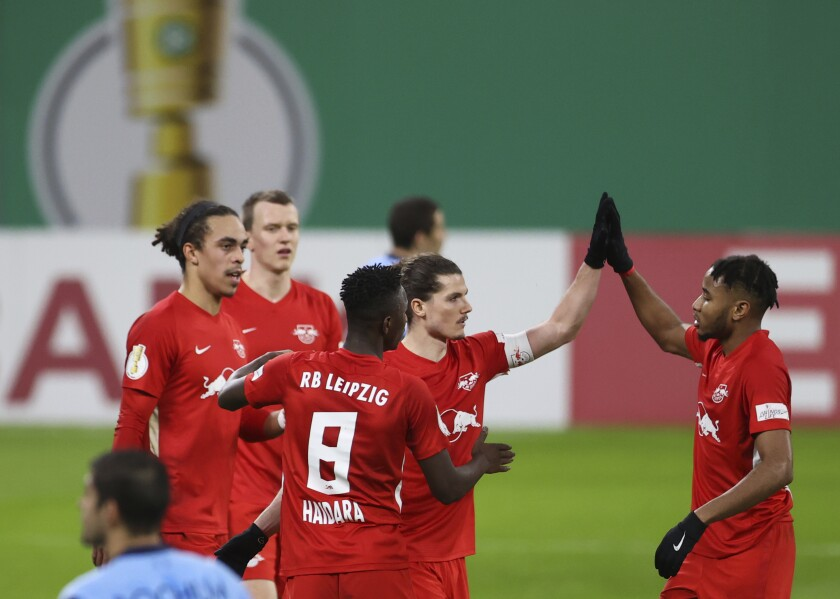 Leipzig's Christopher Nkunku, right, and goal scorer Marcel Sabitzer celebrate the goal during the German Soccer Cup 3rd round match between RB Leipzig and VfL Bochum at the Red Bull Arena in Leipzig, Germany, Wednesday, Feb. 3, 2021. ( Jan Woitas/dpa via AP)