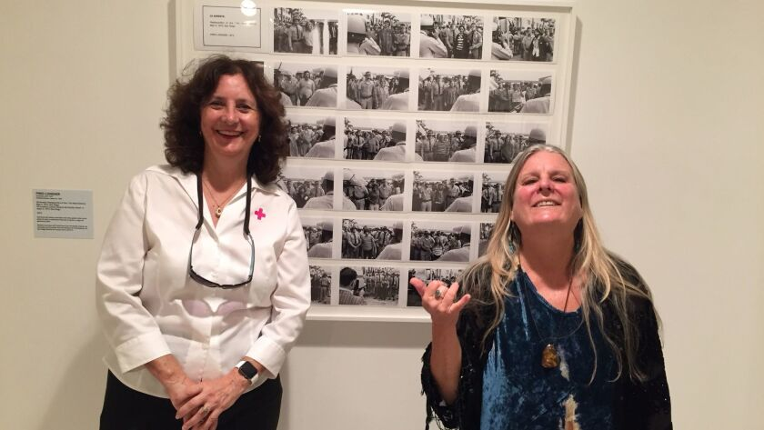 "Former Vietnam War protesters, Linda Blair Forth, left, and Sierra Knight, pose in front of photographer Fred Lonidier's artwork, ""29 Arrests,"" showing 29 protesters as they were about to be taken to jail. Exhibit is at Museum of Contemporary Art San Diego."