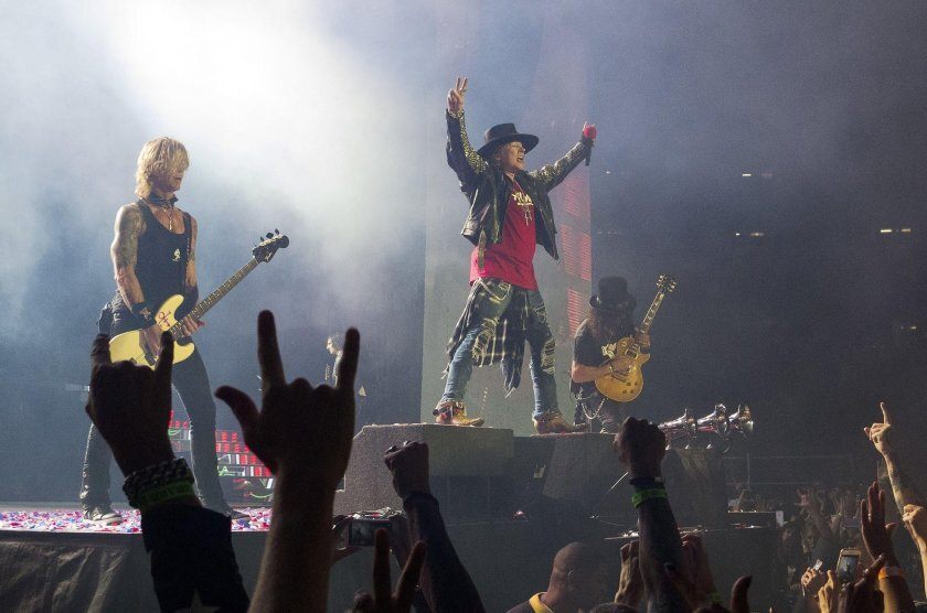 Duff McKagan, left, Axl Rose and Slash stand on platforms of varying height