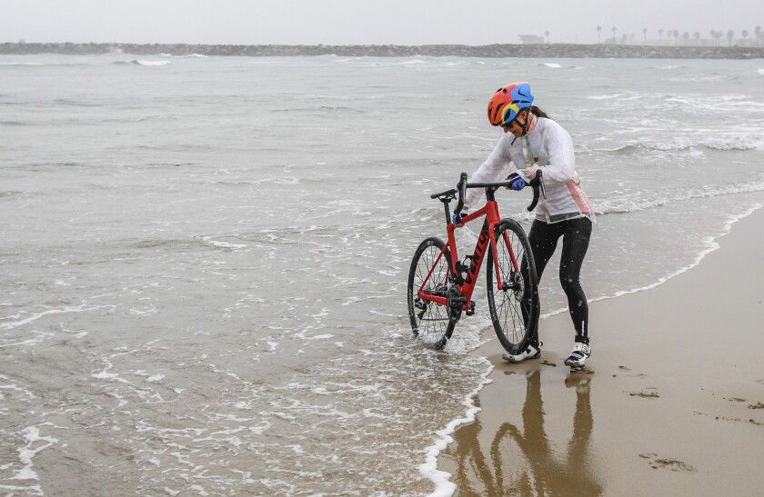 Along with supporters, Isabella de la Houssaye, a stage 4 cancer patient, dips her tire in the Pacific Ocean as she begins her cross country bike ride in Ocean Beach on Tuesday. De la Houssaye, 56, is riding cross country to Jacksonville, Fla., to raise awareness for lung cancer research.