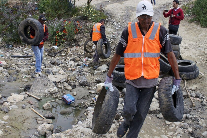 Workers gather discarded tires in Tijuana's Los Laureles Canyon, helping launch a tire recycling pilot program spearheaded by the Imperial Beach-based environmental group, Wildcoast.