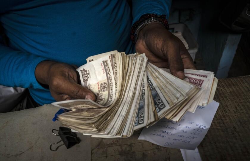 ARCHIVO - En esta fotografía de archivo del 11 de diciembre de 2020, un trabajador muestra un fajo de pesos cubanos en La Habana, Cuba, el viernes 11 de diciembre de 2020. (AP Foto/Ramón Espinosa, Archivo)