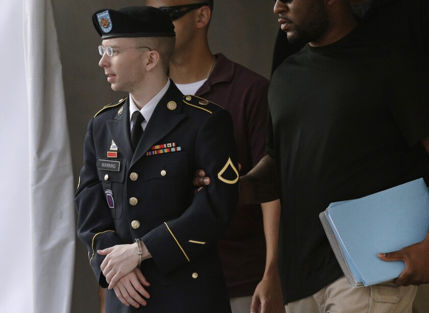 Army Pfc. Bradley Manning, left, is escorted to a security vehicle outside a courthouse in Fort Meade, Md., after leaving court.